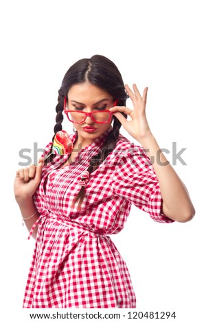 Retro Candy Girl - female student wearing geeky glasses and pigtails, flirting while holding a heart shaped lollipop in her hand - stock photo