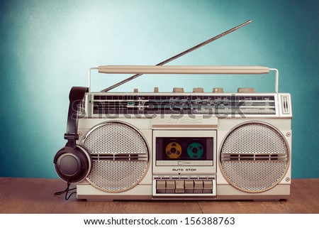Retro cassette ghetto blaster and phones on  table in front mint green background