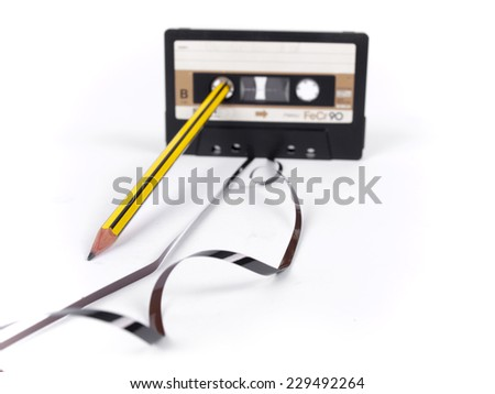retro cassette with loose tape and a pencil to rewind over a white background