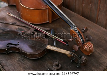 Retro cello and violin on the wooden table need to be repaired or tuned, closeup angled shot