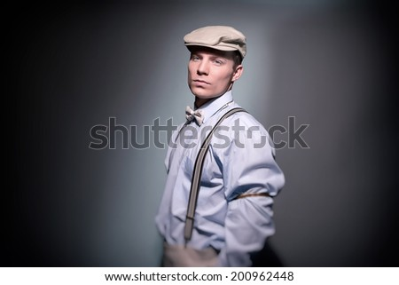 Retro classic dandy fashion man wearing cap with blue shirt braces and bow tie. Studio shot.