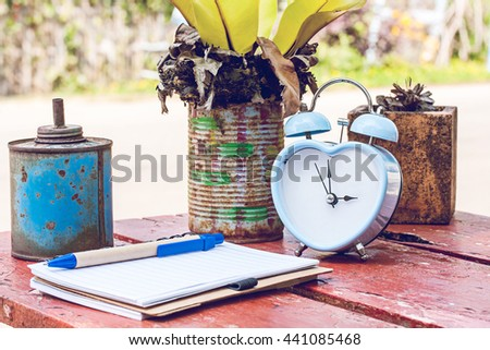 retro clock in garden with notebook and recycle can decorate on table. - stock photo