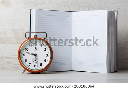 Retro clock with open book on wooden background - stock photo