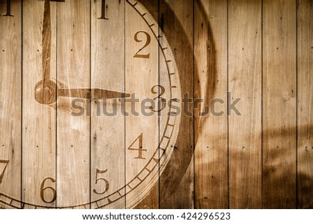 retro closeup clock face on wood background selective focus at number 3 o'clock.