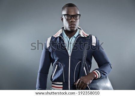Retro college fashion black african man wearing blue jacket, leather bag and glasses. Studio shot against grey. - stock photo