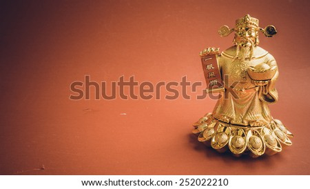 Retro color chinese God of Wealth or prosperity (Cai Shen) statue with shoe-shaped gold ingot (Yuan Bao). Concept for retro auspicious symbol. Slightly defocused close-up shot. Copy space.