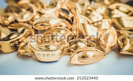 Retro color shoe-shaped metal gold ingot (Yuan Bao), China 20th currency. Concept for Chinese Lunar New Year auspicious symbol. Slightly defocused and close-up shot. Copy space.