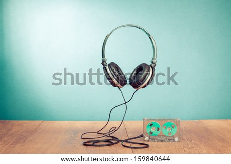 Retro compact cassette with rolls and headphones conceptual photo - stock photo