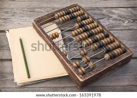 Retro counting abacus, pencil and notepad on a wooden table - stock photo