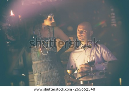 Retro couple.Couple with glasses of red wine in restaurant.Fashion,retro, vintage, tones. Antique picture with scratches and film grain. - stock photo