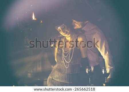 Retro couple.Couple with glasses of red wine in restaurant.Fashion,retro, vintage, tones.Retro couple.Couple with glasses of red wine in restaurant.Fashion,retro, vintage, tones. Antique picture with scratches and film grain. - stock photo