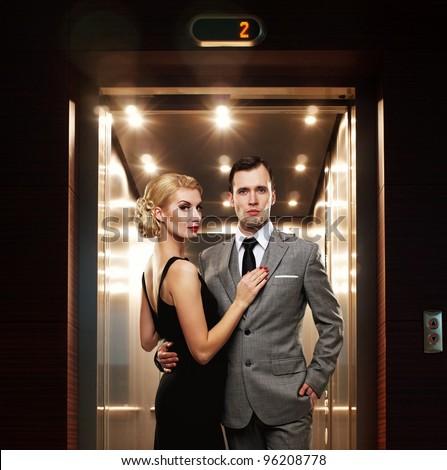 Retro couple standing against elevator. - stock photo