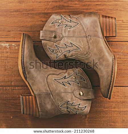 Retro cowboy boots on vintage wooden background - stock photo