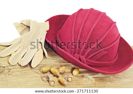 Retro crimson hat and beige gloves on wooden surface isolated on white background - stock photo