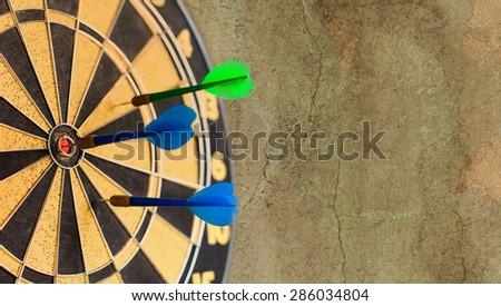 Retro darts board. Blue Dart in bull's eye. Vintage aim. (soft focus, vintage wall background) - stock photo