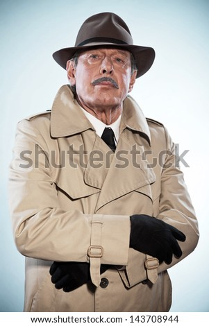Retro detective man with mustache and hat. Wearing raincoat. Studio shot.