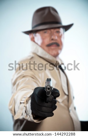 Retro detective with mustache and hat. Holding gun. Studio shot.