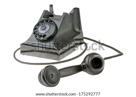Retro dial-up rotary telephone with the handset lying in the foreground turned towards the camera on a white studio background