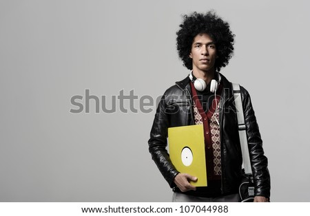 Retro dj portrait in fashion style isolated on grey brackground in studio. Modern music man with afro hairstyle, headphones and vinyl record.