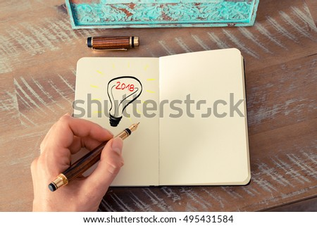 Retro effect and toned image of a woman drawing a lighting bulb with fountain pen on a notebook. Year 2018 symbol for bright idea and business concept, copy space available for text
