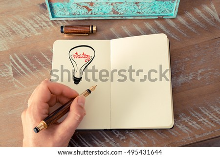 Retro effect and toned image of a woman drawing a lighting bulb with fountain pen on a notebook. STRATEGY symbol and concept, copy space available for text