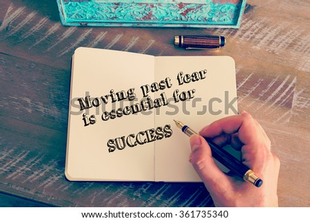 Retro effect and toned image of a woman hand writing a note with a fountain pen on a notebook. Motivational message MOVING PAST FEAR IS ESSENTIAL TO SUCCESS  as concept for self improvement - stock photo