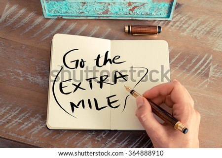 Retro effect and toned image of a woman hand writing a note with a fountain pen on a notebook. Handwritten text GO THE EXTRA MILE, business success concept - stock photo