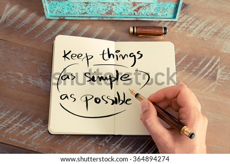 Retro effect and toned image of a woman hand writing a note with a fountain pen on a notebook. Handwritten text  KEEP THINGS AS SIMPLE AS POSSIBLE, business success concept - stock photo