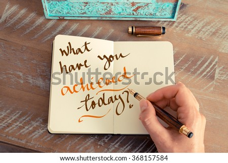 Retro effect and toned image of a woman hand writing a note with a fountain pen on a notebook. Handwritten text WHAT HAVE YOU ACHIEVED TODAY ?, motivation concept - stock photo