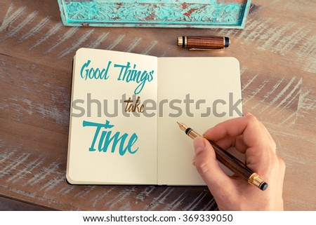 Retro effect and toned image of a woman hand writing a note with a fountain pen on a notebook. Handwritten text GOOD THINGS TAKE TIME, motivation concept - stock photo