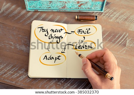 Retro effect and toned image of a woman hand writing a note with a fountain pen on a notebook. Handwritten text Try New Things, Fail, Learn, Adapt Cycle as business concept image - stock photo