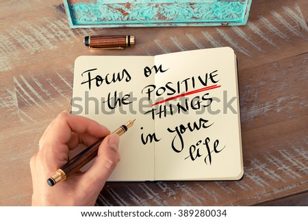 Retro effect and toned image of a woman hand writing a note with a fountain pen on a notebook. Handwritten text Focus On The Positive Things In Your Life as business concept image - stock photo