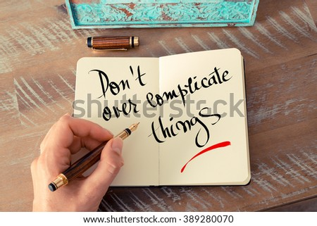 Retro effect and toned image of a woman hand writing a note with a fountain pen on a notebook. Handwritten text Don't Over Complicate Things as business concept image - stock photo