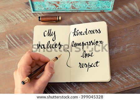 Retro effect and toned image of a woman hand writing a note with a fountain pen on a notebook. Handwritten text My Values Kindness, Compassion, Love, Respect as success and evolution concept image - stock photo