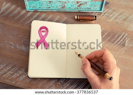 Retro effect and toned image of a woman hand writing a note with a fountain pen on a notebook. Hand drawing of pink ribbon and month October as breast cancer awareness symbol, copy space available