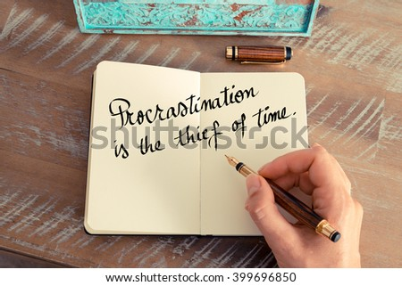 Retro effect and toned image of a woman hand writing on a notebook. Handwritten quote Procrastination is the thief of time as inspirational concept image