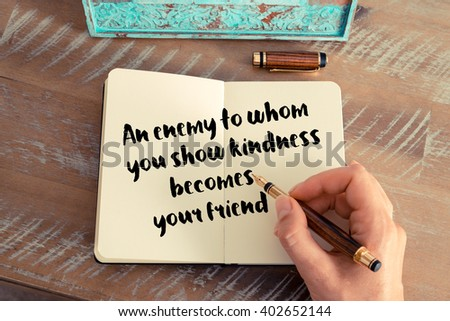 Retro effect and toned image of a woman hand writing on a notebook. Handwritten quote An enemy to whom you show kindness becomes your friend as inspirational concept image - stock photo