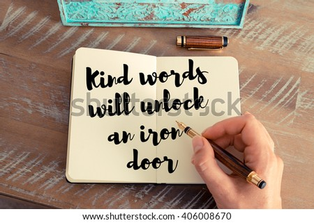 Retro effect and toned image of a woman hand writing on a notebook. Handwritten quote Kind words will unlock an iron door as inspirational concept image - stock photo