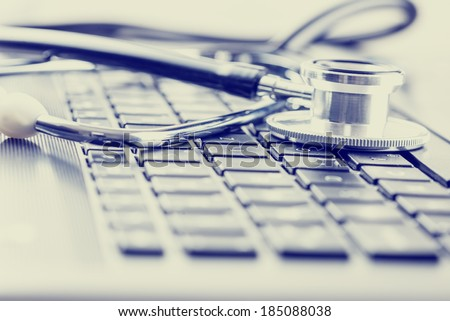 Retro effect faded and toned image of a medical stethoscope on computer keyboard. Concept of computer support. - stock photo