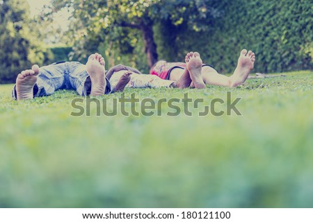 Retro effect faded and toned image of a young caucasian parents and their adopted african child lying in green grass. Concept of family happiness. - stock photo
