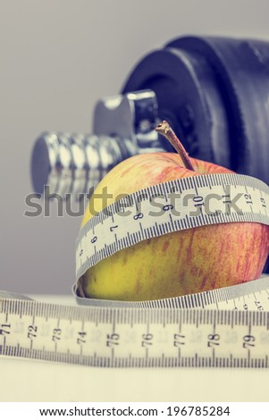 Retro effect faded and toned image of apple wrapped with measuring tape with weights in background.  - stock photo
