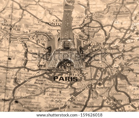 Retro Eiffel Tower on a map of Paris, short focus. - stock photo
