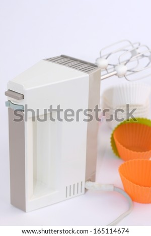 Retro electric hand mixer (eggbeater) with two beaters, Variety of cupcake liners in different  colors in background - stock photo