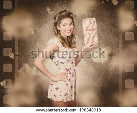 Retro entertainment portrait of a vintage film and cinema pin-up woman holding old popcorn box in front of faded motion picture. Classic movies - stock photo
