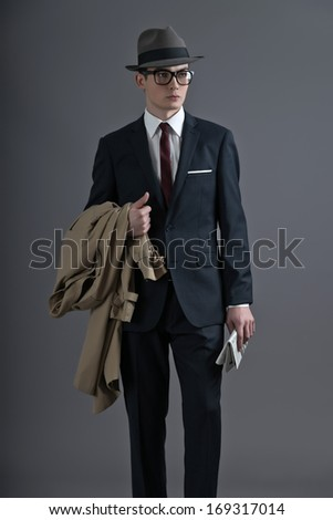 Retro fashion fifties young man with glasses and hat wearing dark suit. Holding a raincoat and newspaper. Studio shot against grey. - stock photo
