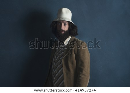 Retro fashion man with beard wearing brown jacket and white hat. Leaning against gray wall. - stock photo