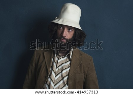 Retro fashion man with beard wearing brown jacket and white hat. Leaning against gray wall.