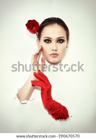 Retro fashion portrait of young woman with one red glove and tulip, image toned. - stock photo