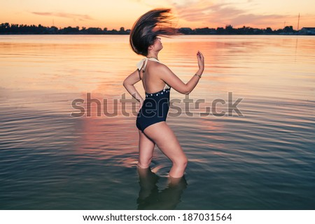 Retro fashion women dancing in water at sunset. - stock photo