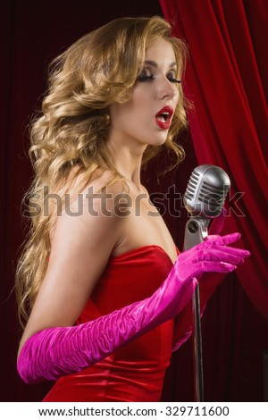 Retro female singer sing holding vintage microphone  - stock photo